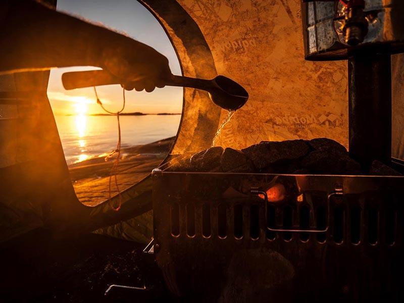 Aufguss auf den Holzofen in einer Mobiba MB-10 Sauna